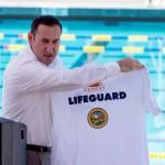 Kevin Kalman presents a lifeguard shirt to John Furbee