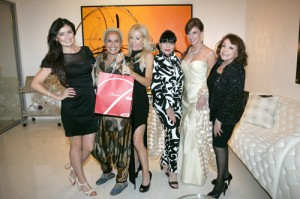 "Shari Belafonte (second from left) is happily left holding the Baccarat gift as Laurie Weitz (to the right of Shari) and the ""Bond Girls"" as spy-themed party benefiting the Palm Springs Art Museum. (Photo by Pat Krause)"